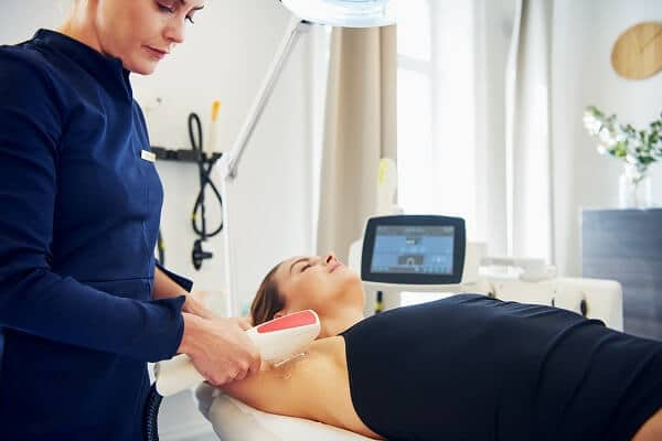 Young female beautician performing a laser hair removal procedure on the underarm of a woman lying on a table in a beauty clinic